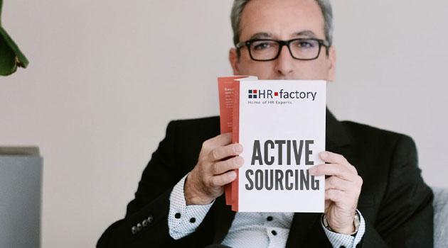 Tamer Celikiz hält ein Active Sourcing Buch hoch