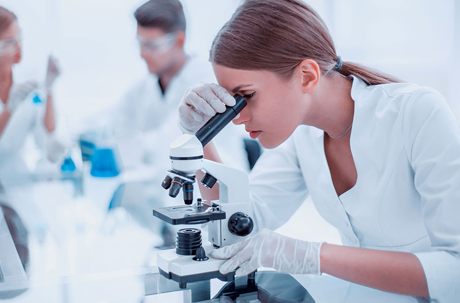 Woman in laboratory at microscope