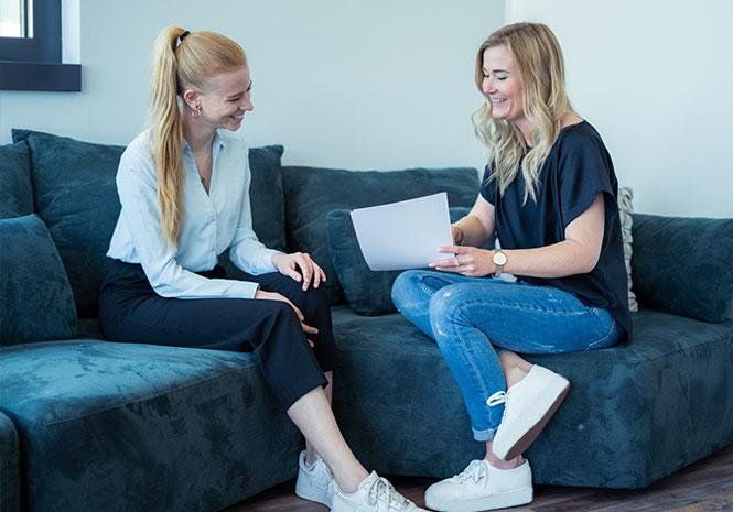 Zwei HR Experts tauschen sich auf einer Couch über Recruiting aus